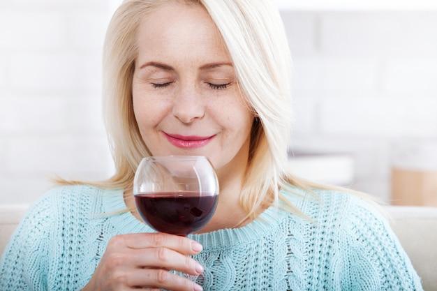 目を閉じて赤ワインを飲んで幸せなブロンド。