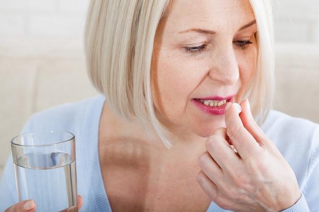 薬、健康管理、人々の概念は、錠剤を取っている中年の女性のクローズアップ。絶縁コンセプト