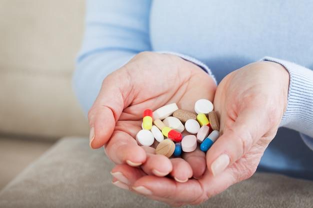 女性の手にたくさんの薬。