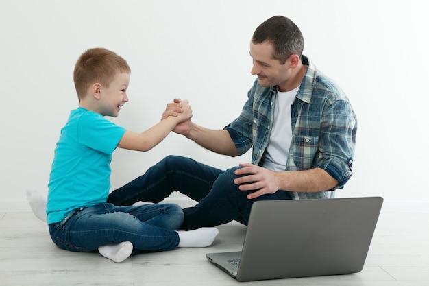 父と息子が自宅で堅木張りの床に座ってラップトップを使用しています。絶縁コンセプト