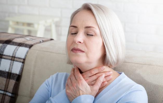 Женщина, страдающая от стресса или головной боли, морщась от боли, когда она держит затылок