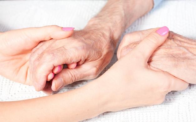 Пожилые руки, удерживаемые другой парой рук