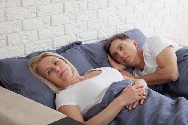 自宅の寝室で不幸な中年夫婦。