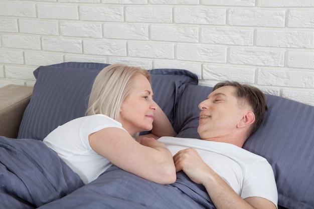 自宅で年配のカップル。ハンサムな老人と魅力的な老婦人がベッドに横たわっている間一緒に時間を過ごすことを楽しんでいます。 。