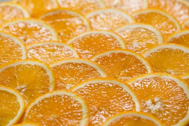 Ярко-оранжевый фон из кусочков сочного апельсина. здоровая пища, фон.