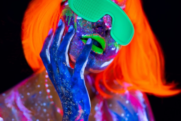 Танцор диско в неоновом свете. фотомодель в неоновом свете, портрет красивой модельной девушки с флуоресцентным макияжем, боди-арт дизайн в ультрафиолетовом свете, раскрашенное лицо, красочный макияж, на черном фоне