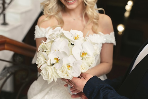 花嫁の手の中の豪華な白いウェディングブーケ