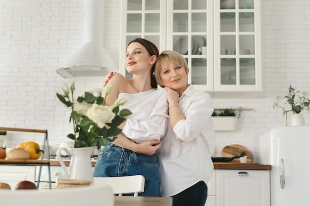 Портрет крупным планом двух симпатичных привлекательных прекрасных нежных жизнерадостных женщин мама взрослой дочери проводит время день вместе в белом свете интерьер дома квартира квартира в помещении