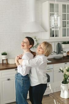Счастливая любящая старшая зрелая мать и взрослая дочь смеются, обнимая,