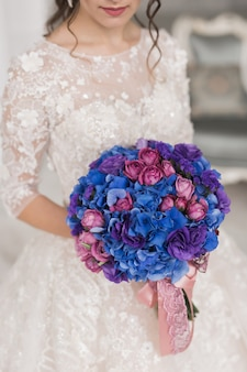 花嫁の手の中の青、ピンク、紫の花の明るいウェディングブーケ。