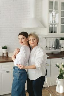 Портрет двух симпатичных привлекательных милых нежных жизнерадостных женщин мама взрослой дочери вместе проводит время на кухне