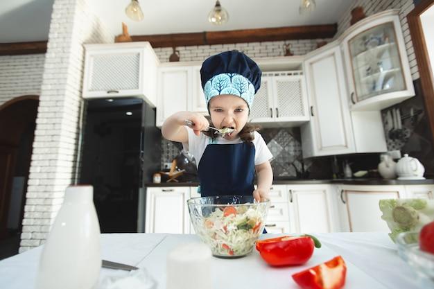 エプロンとシェフの帽子をかぶった子供がキッチンで野菜サラダを食べています