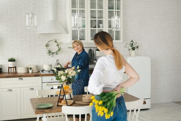 Красивая взрослая дочь прячет цветы за спиной для своей взрослой мамы. день матери, женский праздник.