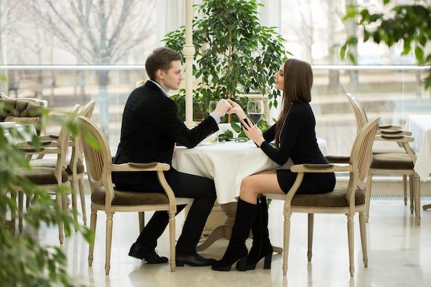 レストランで女の子の手を握ってハンサムな男