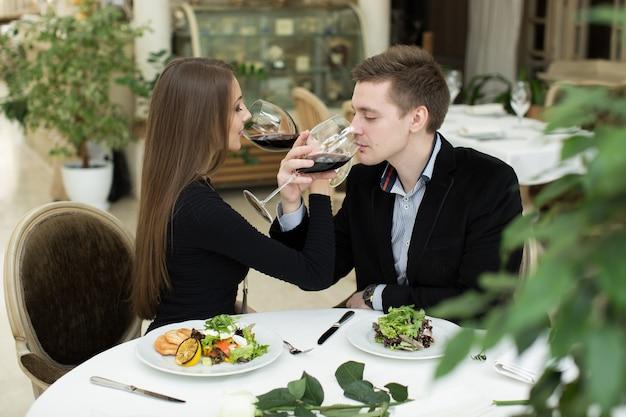 レストランで赤ワインを祝う若い幸せな好色なカップル。