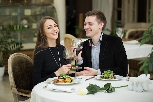 ワインとサラダを楽しんで、レストランで幸せなカップル