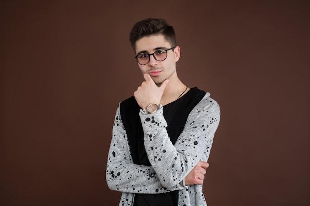 うつ病の若い男。スタイリッシュな男子生徒は丸い眼鏡をかけ、トレンディなヘアスタイルを持ち、自信を持って見え、茶色の壁に孤立しています。