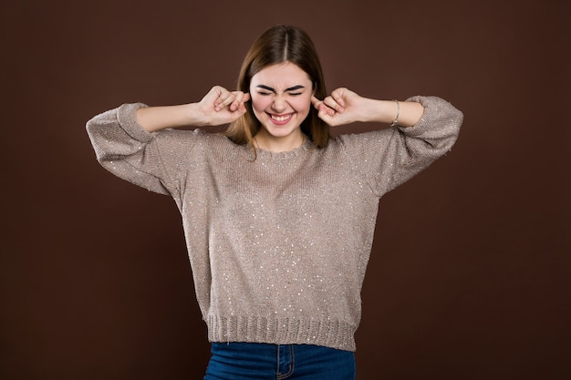 Крупным планом портрет злой подчеркнул молодая женщина затыкать уши пальцами, раздраженный с громким раздражающим шумом, с головной болью или мигренью. негативные эмоции человека