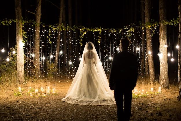 Свадебная ночь. встреча молодоженов, жениха и невесты в хвойном сосновом лесу со свечами и лампочками.