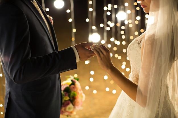 Вечерняя свадебная церемония. невеста и жених, взявшись за руки на огни и фонари.