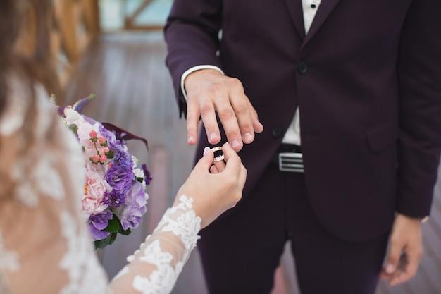 Невеста надевает кольцо на палец жениха.