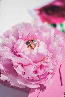 Золотые обручальные кольца на фоне цветов пиона. свадебная открытка с цветами пион крупным планом.