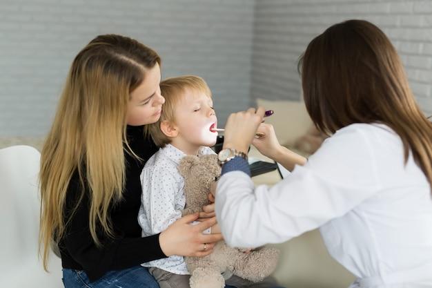 医師が子供の喉を調べる