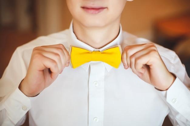 結婚式の衣装と黄色の蝶ネクタイで幸せな笑顔の若い男の肖像画。閉じる。手、唇。