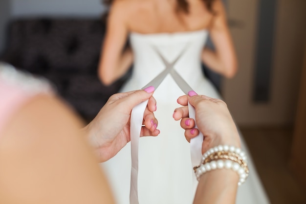 新婦付添人は花嫁のウェディングドレスの後ろに蝶結びを作る
