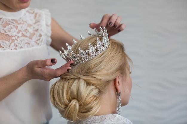 スタイリストは王冠の花嫁を着ています