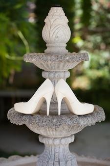 緑の自然の結婚式の靴。噴水。