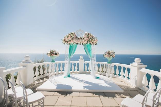 Элегантная свадебная арка со свежими цветами, вазами на берегу океана и голубым небом.