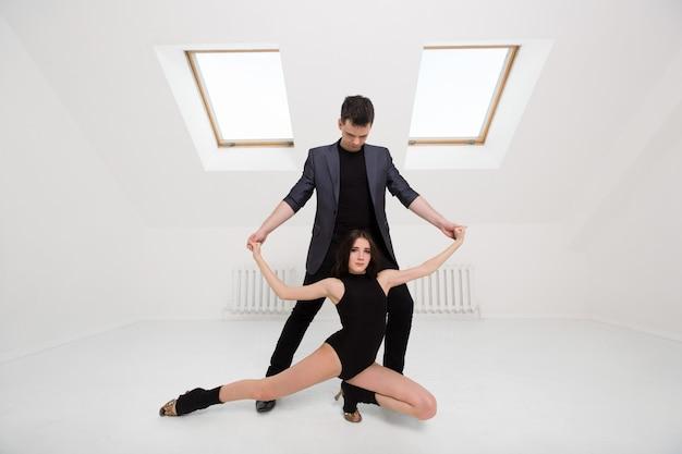 白い部屋でバチャータを踊る美しいカップル