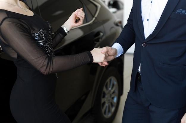 新しい所有者に車のキーを与える店員