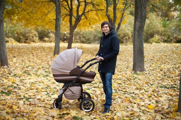 秋の公園で歩く若い男