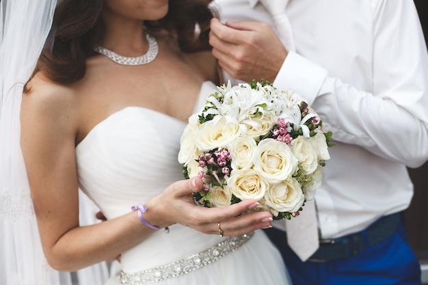 Жених и невеста держит свадебный букет