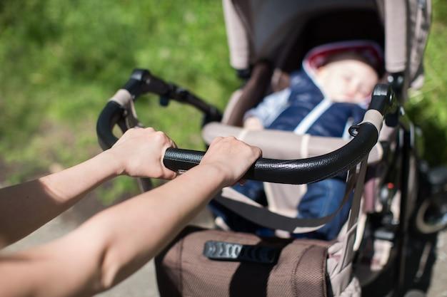 若い母親が歩いて公園でベビーカーを押す