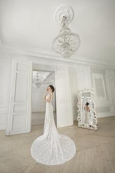 Красивая невеста позирует в свадебном платье в белой фотостудии