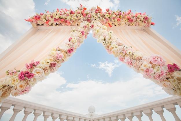 Свадебная арка персикового цвета с цветами на фоне моря
