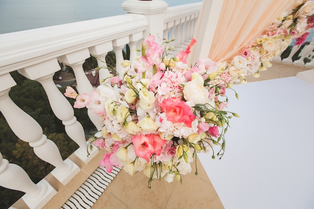Свежие цветы в вазе возле свадебной арки на фоне моря.