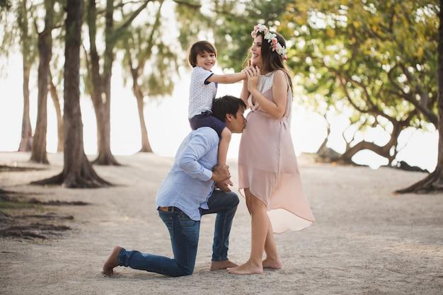 Счастливая семья беременных, с удовольствием в природе. сын на плечах твоего отца. папа целует свою беременную жену в живот.