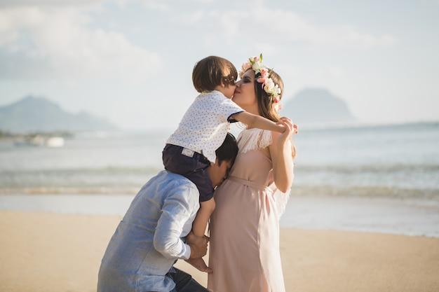 妊娠中の女性、赤ちゃん、ビーチでの混血男