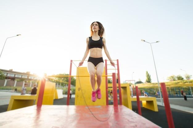 Фитнес, спорт, обучение, парк и образ жизни концепция - женщина, работающая с скакалкой на открытом воздухе