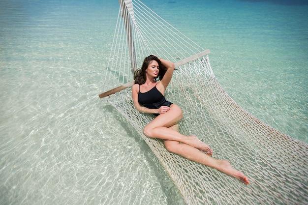 島の熱帯のビーチでハンモックの女性