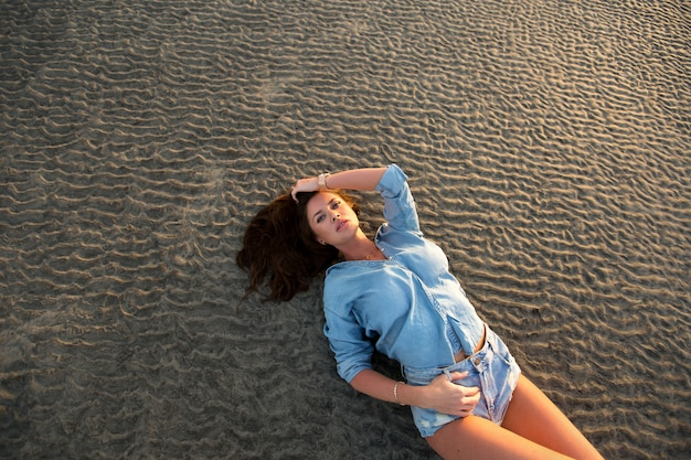 夕暮れ時、砂の上に横たわる若い女性