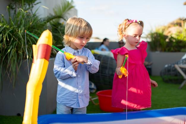 Брат и сестра играют на рыбалке в детском бассейне