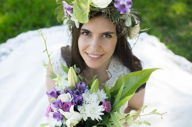 手に花束と花輪の美しい若い花嫁