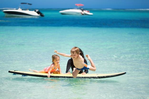 Близнецы, мальчик и девочка с мамой, серфинг в океане на доске