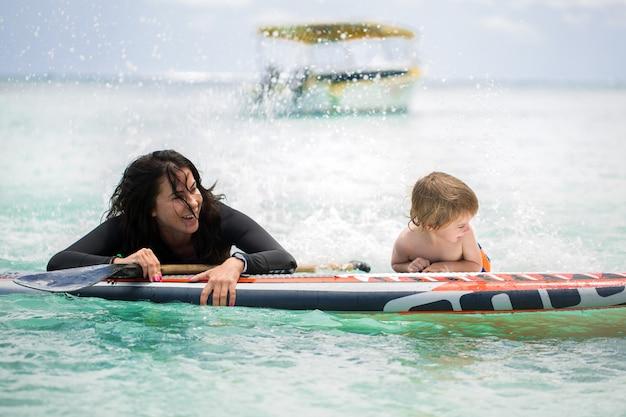 ママと息子が黒板に海でサーフィンをしている