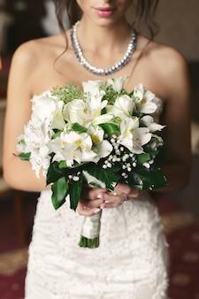 Роскошный белый свадебный букет в руках невесты